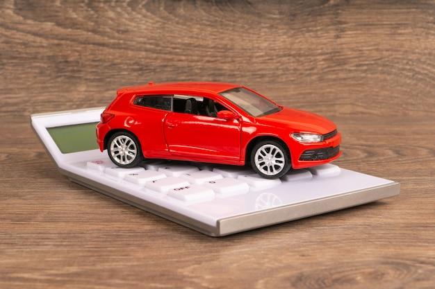 Rotes auto und taschenrechner auf holztisch, mieten oder kaufen