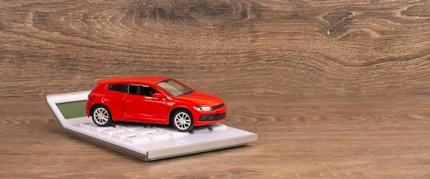 Rotes auto und weißer rechner auf holztisch, panoramaaufnahme