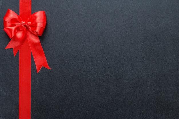 Rotes band an einer schwarzen tafel. feierlicher hintergrund mit kopierraum
