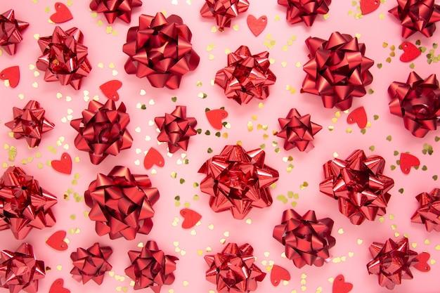 Rotes band beugt muster, abstrakten rosa hintergrund mit herzen. valentinstag, geburtstag, geschenkbögen. flach liegen