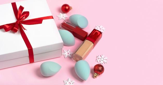 Rotes band der weißen geschenkbox der weihnachten für frauensatz des dekorativen kosmetikmake-ups und der schneeflocken