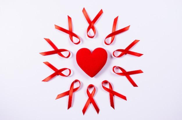 Rotes band des aids-bewusstseins um rotes herz auf weißem hintergrund