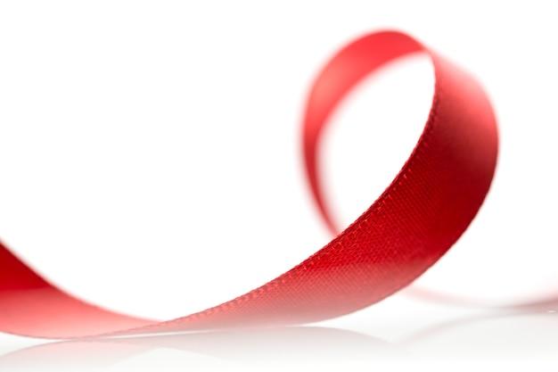 Rotes band des schönen stoffes auf weißer oberfläche