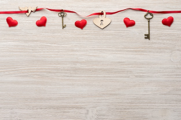 Rotes band geht durch zwei weinleseschlüssel und ein herzschloss auf hölzernem hintergrund für valentinstag
