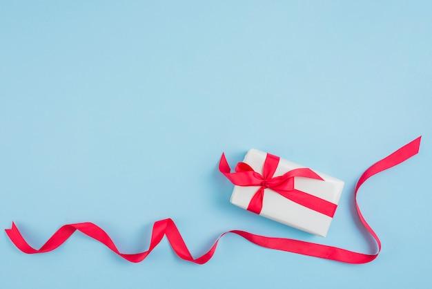 Rotes band in der nähe von geschenkbox