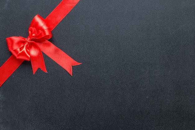 Rotes band mit einer schleife auf einer schwarzen tafel. feierlicher hintergrund mit kopierraum