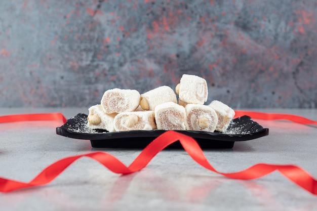 Rotes band um eine schwarze platte mit marshmallows auf marmoroberfläche gelegt
