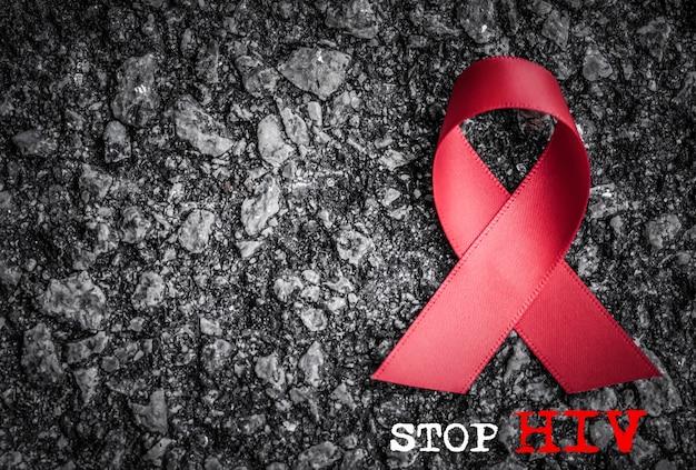 Rotes bandbewusstsein auf dunklem hintergrund für welt aids-tageskampagne
