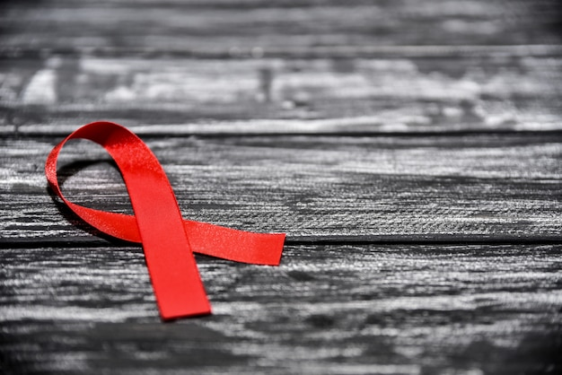 Rotes bandbewusstsein auf schwarzem hölzernem hintergrund für welthilfetag, welt-aids-schutzimpfungstag. tiefenschärfe.