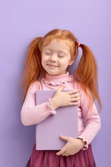 Rotes behaartes kleines mädchen lokalisiert. süßes kleines mädchen in freizeitkleidung umarmt buch, mit geschlossenen augen. schule, bildungskonzept.