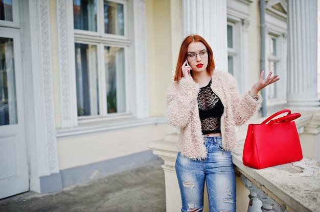 Rotes behaartes mädchen mit roter handtasche warf nahe weinlesehaus auf und sprach am handy.