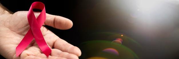 Rotes bewusstseinsband in den händen eines mannes auf einer dunklen oberfläche mit einem platz für text für das konzept des welt-aids-tages