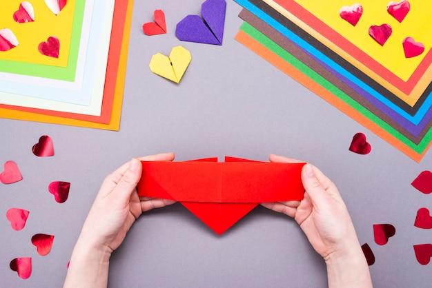 Rotes blatt papier für handarbeit. aus einem blatt rotem papier ein lesezeichenherz machen