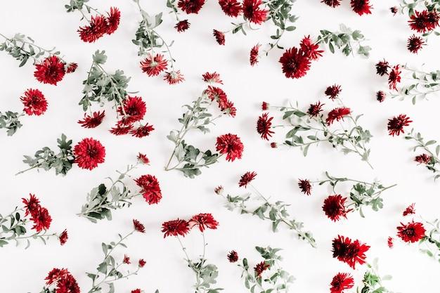Rotes blumenmuster auf weißem hintergrund. flache lage, ansicht von oben