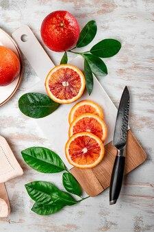 Rotes blutiges orange, das in scheiben auf einem vertikalen foto des weißen schneidebretts geschnitten wird