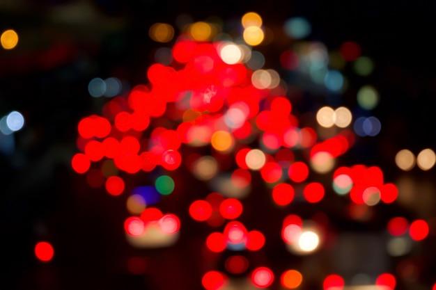 Rotes bokeh licht vom auto auf straße in der stadt in der nacht. unscharf gestellt von nachtverkehr.