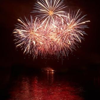 Rotes buntes feiertagsfeuerwerk auf dem schwarzen himmel.