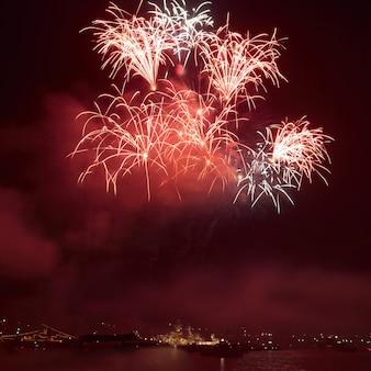 Rotes buntes feiertagsfeuerwerk auf dem schwarzen himmel