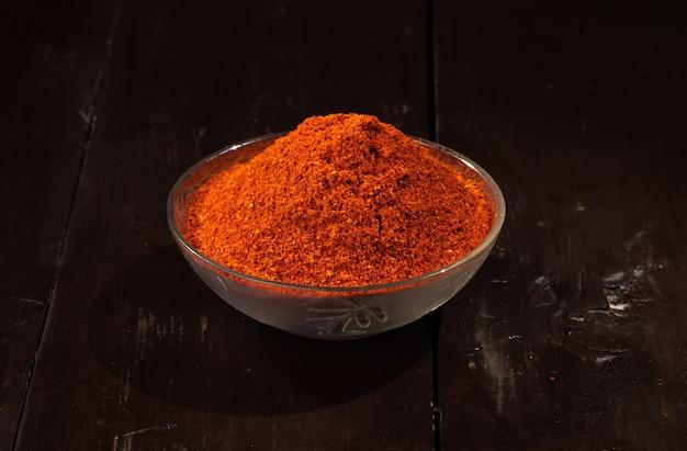Rotes chilipulver aus indischen getrockneten roten chilis, indischem gewürz und indischer lebensmittelzutat auf holz