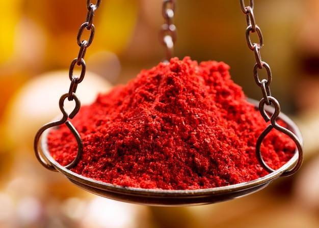Rotes chilipulver in vintage eisenschalengewichten