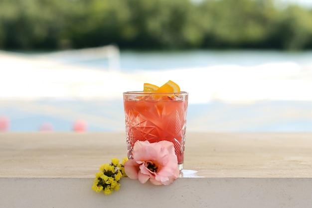 Rotes cocktail in einem glas mit einer orangenscheibe. mit blumendekor