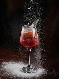 Rotes cocktail mit eis und kirsche in einem transparenten glas. puderzucker streut auf einen cocktail