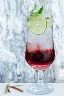 Rotes cocktail mit zitronenscheiben und tadellosen blättern.