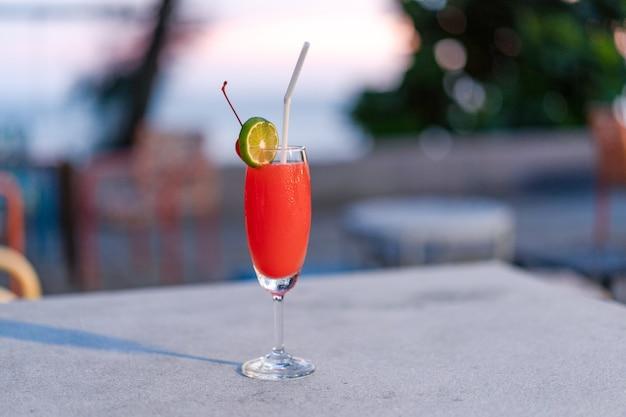 Rotes cocktailglas am platz im freien in thailand resort.
