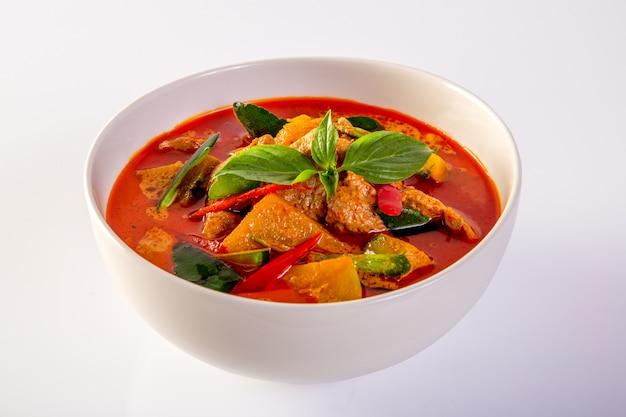 Rotes curry-schweinefleisch und gemüse (panaeng), auf einem weißen hintergrund