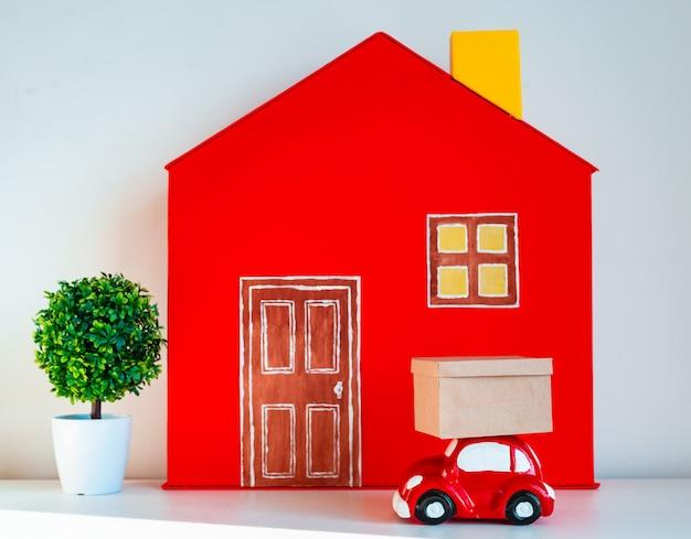 Rotes dekoratives haus mit spielzeugauto