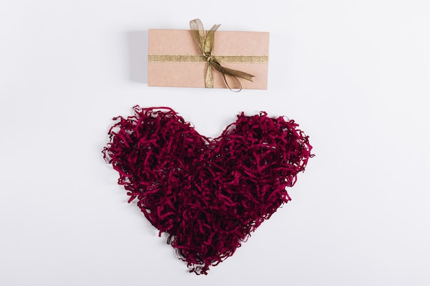 Rotes dekoratives herz und ein kasten mit einem geschenk auf einem weißen hintergrund