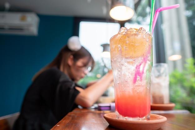 Rotes durchschlagsodatrunk mit orange silce auf dem glas mit person entspannen sich im hintergrund