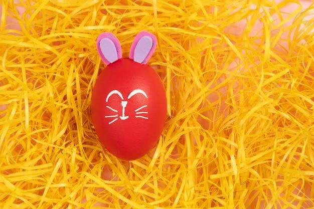 Rotes ei mit osterkaninchen auf gelben strohspänen gezeichnet