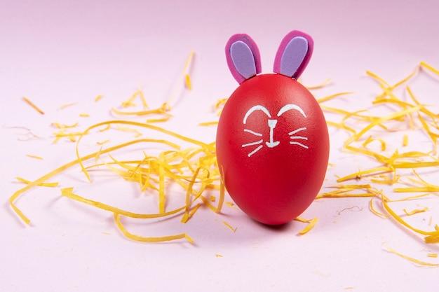 Rotes ei mit osterkaninchen auf gelben strohspänen gezeichnet Premium Fotos