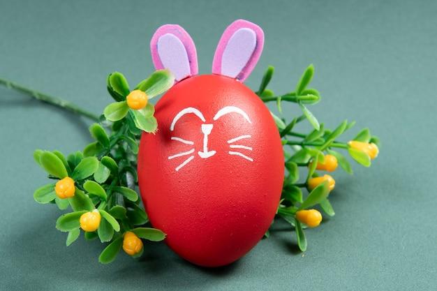 Rotes ei mit osterkaninchen gezeichnet auf grüner wand Premium Fotos