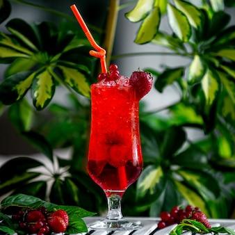 Rotes erdbeercocktail geschmückt mit erdbeere und moosbeere