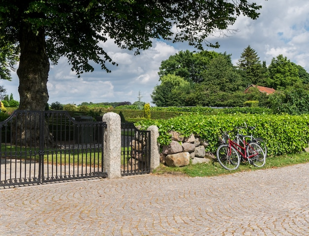 Rotes fahrrad am eisentor im park