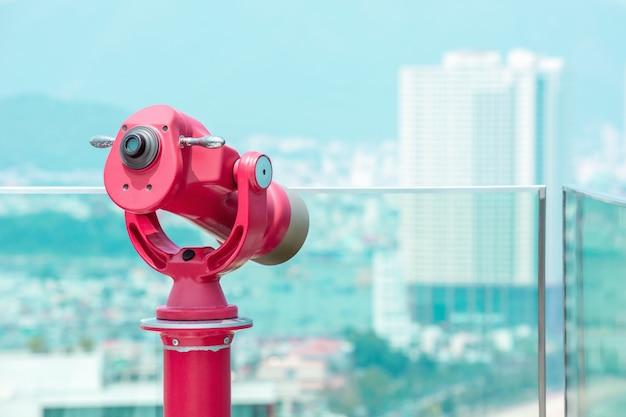 Rotes fernglas auf dem dach für einen überblick über die stadt.