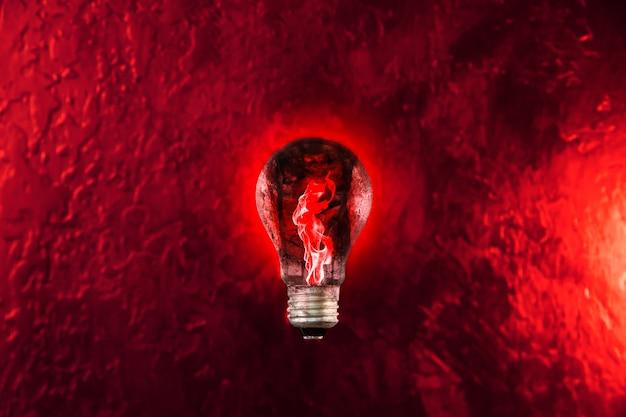 Rotes feuer in der glühbirne. neues ideenkonzept.