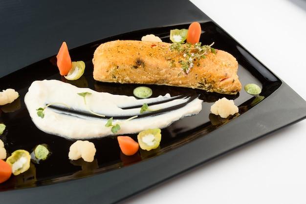 Rotes fischfilet mit gemüse, kräutern und weißer sauce auf einem schwarz glänzenden teller. gourmet-restaurant gericht.