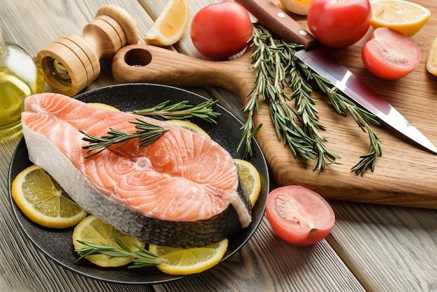 Rotes fischsteak mit gewürzen und gemüse zutaten zum kochen von lachssteak nahaufnahme