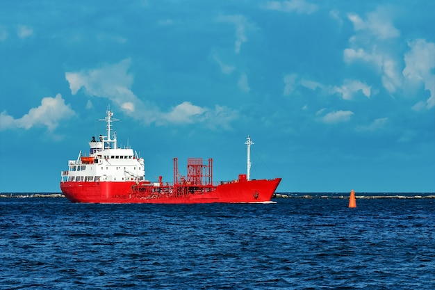 Rotes frachttankerschiff, das durch den fluss bewegt
