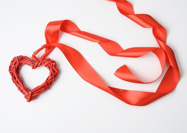 Rotes geflochtenes herz und verdrehtes seidenband auf weißem hintergrund, draufsicht