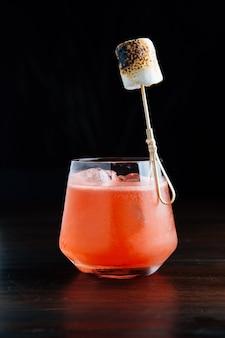 Rotes gefrorenes cocktail mit gebranntem eibisch in trinkglas auf holztisch mit schwarzem hintergrund.