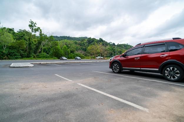 Rotes geländewagenauto geparkt auf betonparkplatz automobilindustrie gebrauchtwagengeschäftskopierraum