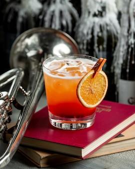 Rotes gelbes orangensaftglas mit schaum auf einem buch.