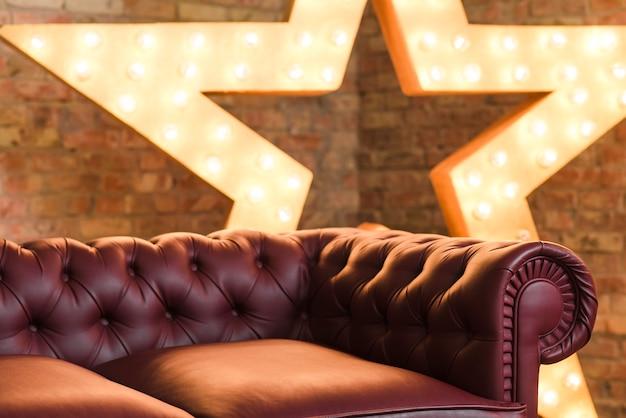 Rotes gemütliches sofa vor glühendem stern gegen backsteinmauer