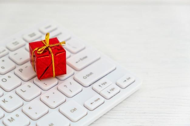 Rotes geschenk auf computertastatur - weihnachts-online-einkaufskonzept