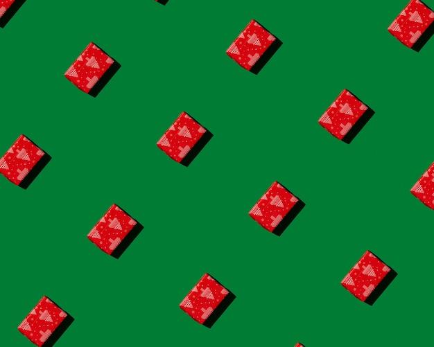 Rotes geschenk auf grünem hintergrundmuster