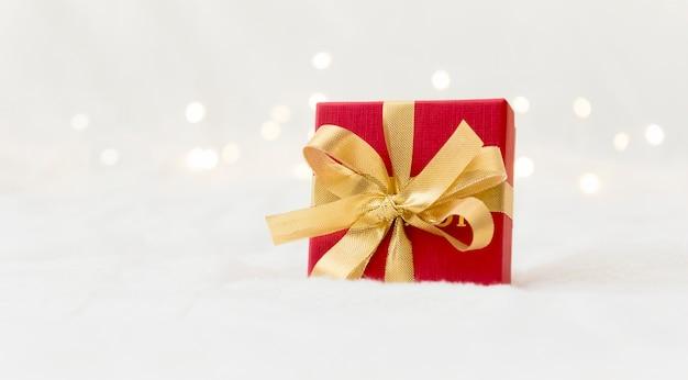 Rotes geschenk mit einer goldenen schleife auf einem hellen hintergrund